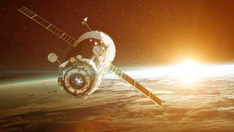 Avaruudessa oleva satelliitti ja taustalla maapallo.