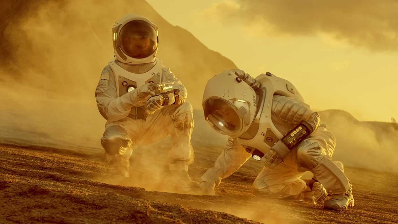 Kaksi astronauttia tutkimassa höyryävää planeetan pintaa.