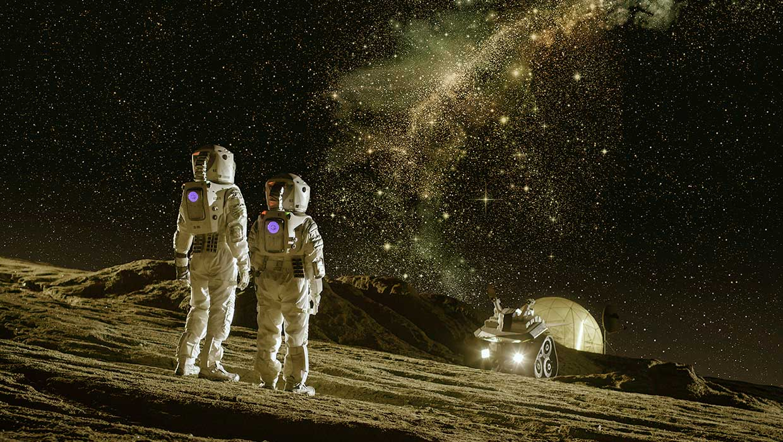Kaksi astronauttia katsovat kuun pinnalla kaunista tähtijonoa.