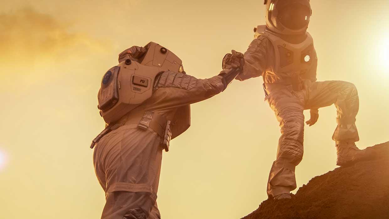 Astronautti auttaa kädellään toista astronauttia nousemaan mäen päälle kuun pinnalla.