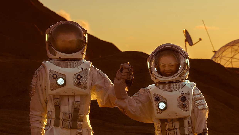Kaksi astronauttia nostavat yhdessä kädet ilmaan onnistumisen merkiksi.